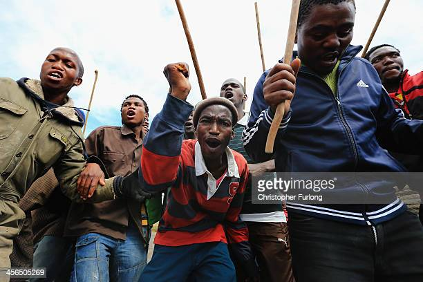 Xhosa men fighting with sticks cross the road during a manhood ceremony as people wait for the funeral cortege of former South African president...