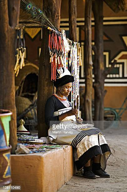 xhosa woman in traditional dress, doing beadwork. lesedi cultural village near johannesburg, south africa. - xhosa culture stock photos and pictures