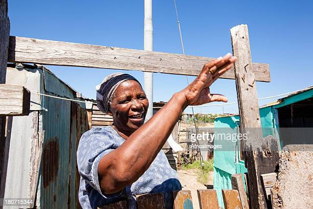 xhosa woman waving to her friend over the fence - xhosa culture stock photos and pictures