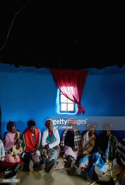 Xhosa women sit inside a house in the village where President Nelson Mandela was born called the Mvezo Komkhulu or 'great place' on December 13 2013...
