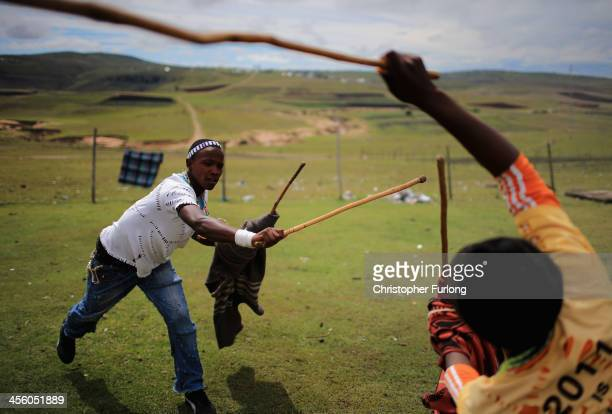Xhosa youths fight with sticks as they take part in a manhood ceremony in Qunu ahead of the funeral of Nelson Mandela on December 13 2013 in Qunu...