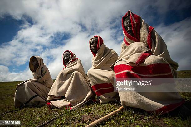Xhosa youths sit on a hillside overlooking the home town of former South African President Nelson Mandela before his funeral cortege arrives at his...