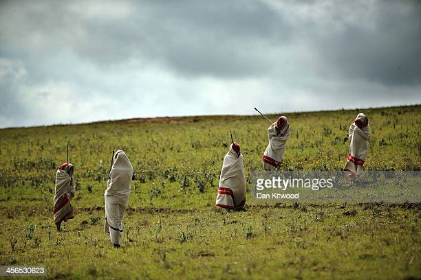 Xhosa youths walk over a hillside overlooking the home town of former South African President Nelson Mandela before his funeral cortege arrives at...