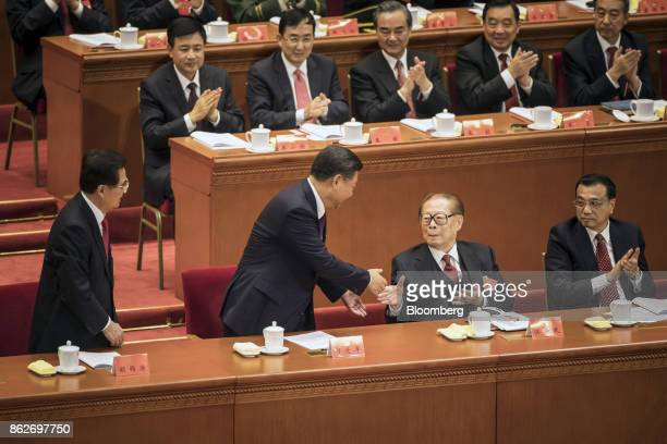 Xi Jinping, China's president, center left, shakes hands with Jiang Zemin, China's former president, after delivering his speech as Li Keqiang,...