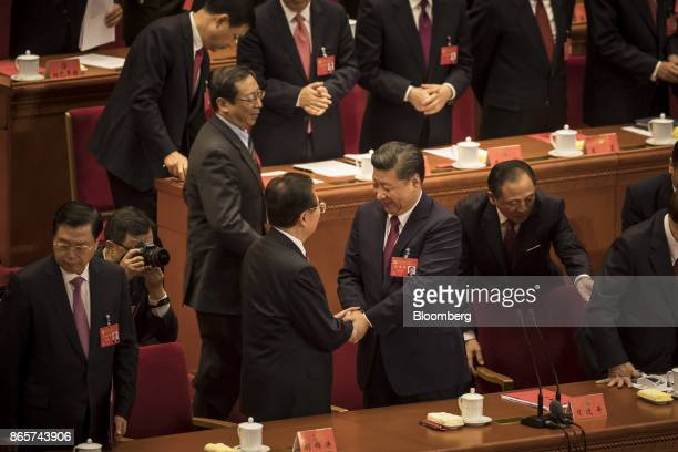 Xi Jinping China's president center right shakes hands with Hu Jintao China's former president at the conclusion of the closing session of the 19th...