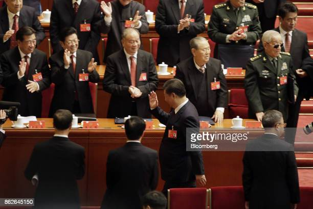 Xi Jinping, China's president, center, walks past delegates applauding after he delivered his speech at the opening of the 19th National Congress of...