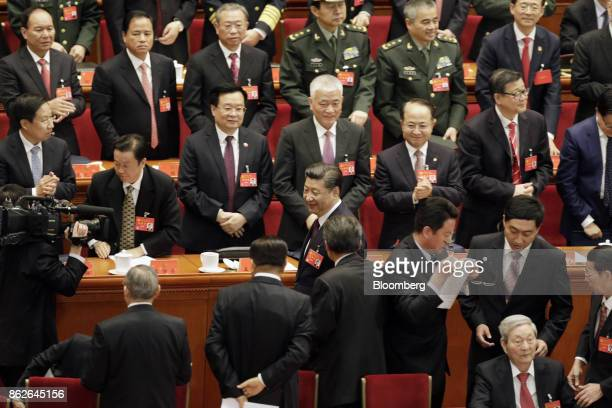 Xi Jinping, China's president, center, walks past delegates standing after he delivered his speech at the opening of the 19th National Congress of...