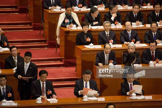 Xi Jinping China's president front row second right and Li Keqiang China's premier front row right look at their ballots as Li Zhanshu member of the...