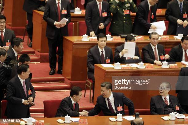Xi Jinping, China's president, front row second right, shakes hands with Hu Jintao, China's former president, as Jiang Zemin, China's former...