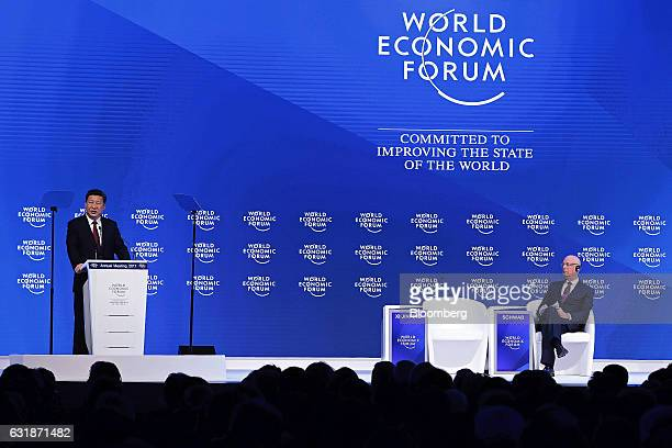 Xi Jinping China's president left speaks as Klaus Schwab chairman of the World Economic Forum listens during the opening plenary session of the World...