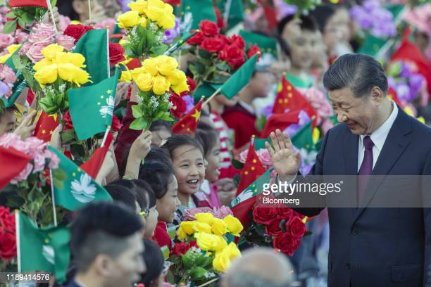 Xi Jinping, China's president, waves to children waving the flags of China and the Macao Special Administrative Region after arriving at Macau...