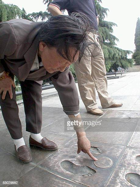 Xia Shuqin points to her footprints together with other survivors at the Monument for the Victims of the Nanjing Massacre in Nanjing 01 June 2005 Xia...