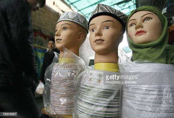 Pedestrians walk along an alleyway in Xian's Muslim quarter pass a display of Islamic head gear for sale 08 February 2007 in Xian capital of...