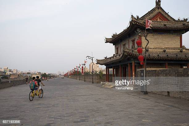 Xi'an,China-Augest 22,2016: Young people riding the bicycle on the ancient Xi'an city wall
