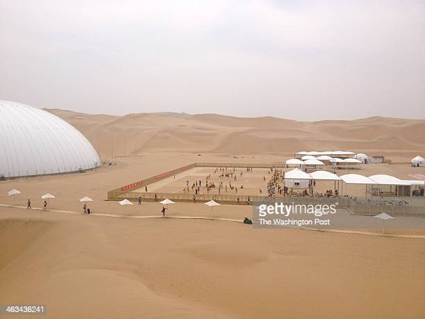 Xiangshawan CHINA JULY The theater left and volleyball court complex viewed from one of the dunes in the Xiangshawan desert park The floor of the...