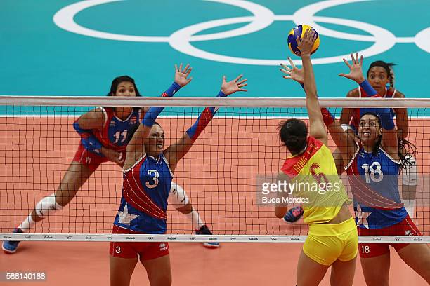 Xiangyu Gong of China spikes the ball against Lynda Morales and Vilmarie Mojica of Puerto Rico during the women's qualifying volleyball match between...