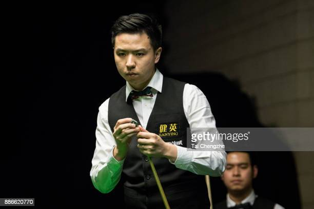 Xiao Guodong of China chalks the cue during his third round match against Noppon Saengkham of Thailand on day 9 of 2017 Betway UK Championship at...