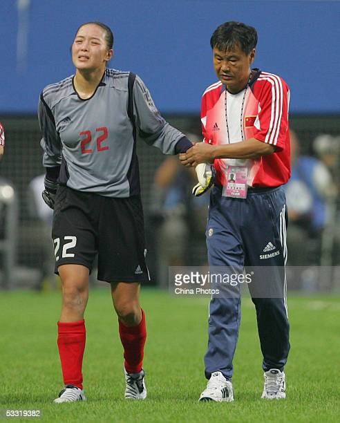 Xiao Zhen , goalkeeper of Chinese Women Football Team, is supported by the team's head coach Pei Encai as she leaves the playing field after an...
