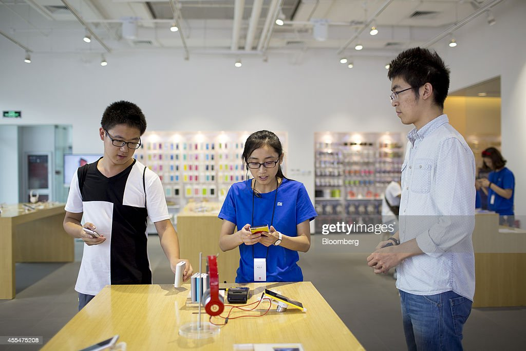 A Xiaomi Corp. employee, center, serves customers at the company's showroom in Beijing, China, on Friday, Sept. 12, 2014. Xiaomi Chief Executive Officer Lei Jun plans to boost global smartphone sales fivefold to 100 million units next year. Photographer: Brent Lewin/Bloomberg via Getty Images