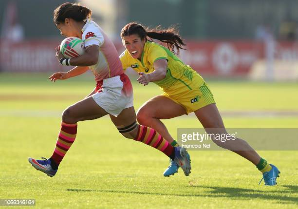 Xiaoqian Liu of China is tackled by Charlotte Caslick of Australia on day one of the Emirates Dubai Rugby Sevens HSBC World Rugby Sevens Series at...