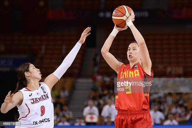 Xiaoxia Chen of China handles the ball while Chinatsu Yamamoto of Japan in action in finals match between Japan and China during the 2015 FIBA Asia...