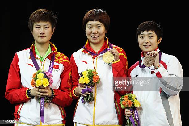 Xiaoxia Li of China stands on the podium after winning the Gold medal Ning Ding of China the Silver and Tianwei Feng of Singapore the Bronze...