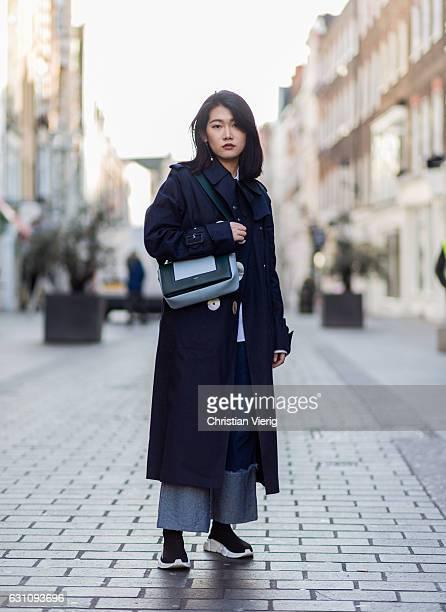 Xiaoyu Hu wearing a navy Mackintosh JW Anderson coat Celine bag wide leg denim jeans Balenciaga sneakers during London Fashion Week Men's January...