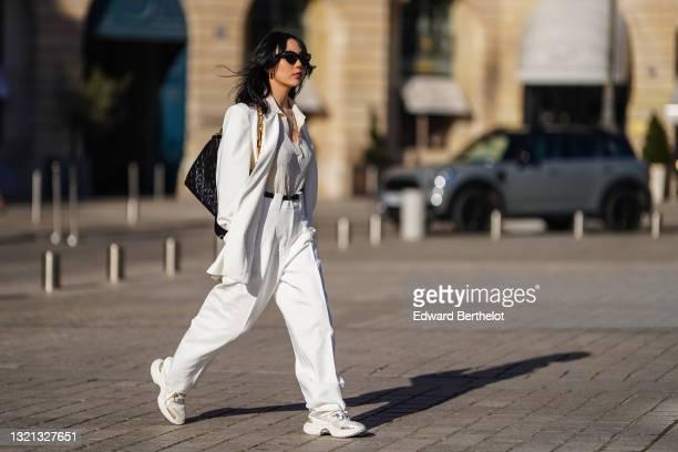 Xiayan wears black Bottega Veneta sunglasses, silver earrings, a silver chain necklace, a white V-neck silk gown, a white long oversized Sundarbay...