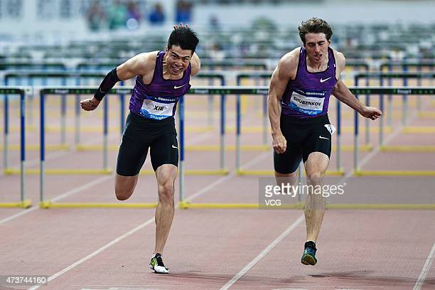 Xie Wenjun of China and Sergey Shubenkov of Russia compete in the men's 110m hurdle event during the Shanghai IAAF Diamond League 2015 meeting at...