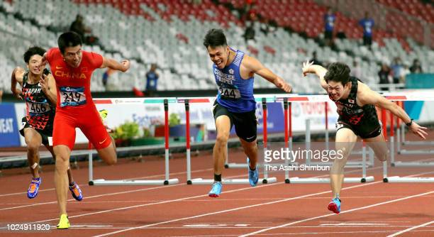 Xie Wenjun of China Chen Kueiru of Chinese Taipei and Shunya Takayama of Japan compete in the Men's 110m Hurdles at the GBK Main Stadium on day ten...
