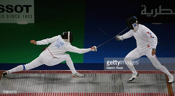 Xie Yongjun of China competes with Kim Seung Gu of Republic of Korea in the Men's Team Epee Gold Medal match during the 15th Asian Games Doha 2006 at...