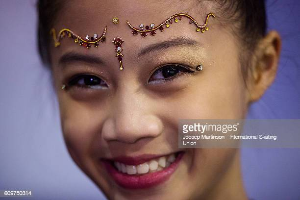 Xin Yi Loke of Singapore poses for a photograph at kiss and cry during the Junior Ladies Short Program on day one of the ISU Junior Grand Prix of...