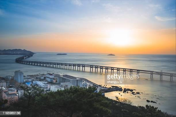 xinghai bay bridge sunrise; - bridgetown barbados stock pictures, royalty-free photos & images