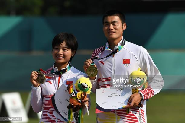 Xinyan Zhang and Tianyu Xu of China celebrate on the podium during Recurve Mixed Team Archery victory ceremony on day nine of the Asian Games on...