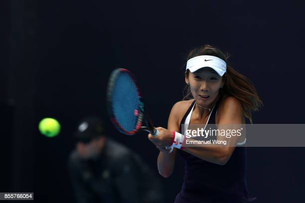 Xinyu Gao of China returns a shot to Magda Linette of Poland on day one of the 2017 China Open at the China National Tennis Centre on September 30...