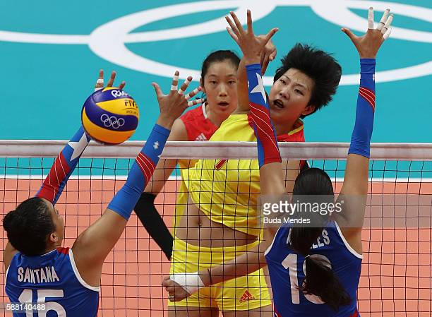 Xinyue Yuan of China spikes the ball against Daly Santana and Lynda Morales of Puerto Rico during the women's qualifying volleyball match between the...