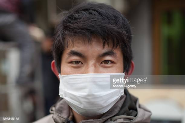 Xiwen Qing 26 years old from Gansu Province poses for a portrait at Houhai Nanyan in Beijing China on March 22 2017 Heavy smog has become a major...