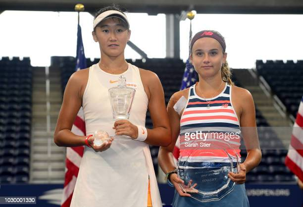 Xiyu Wang of China and Clara Burel of France pose for a photo following the Junior Girl's finals championship match on Day Fourteen of the 2018 US...