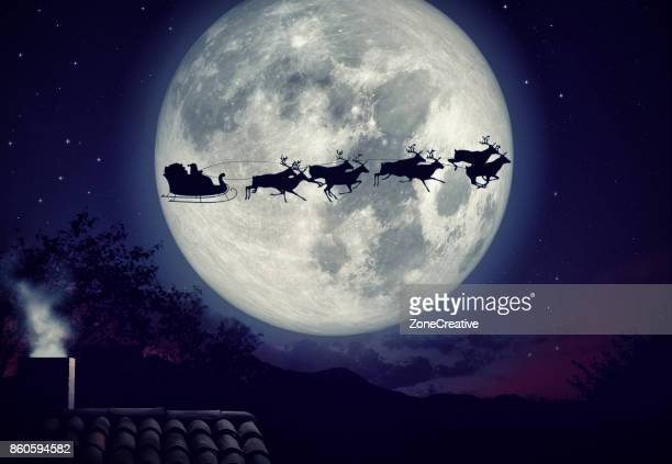 xmas eve night with rooftop and smoky chimney with Santa Claus sleight and reindeer silhouette flying by the moon to bring gifts and presents with text space to place logo or copy.Christmas present greeting post card
