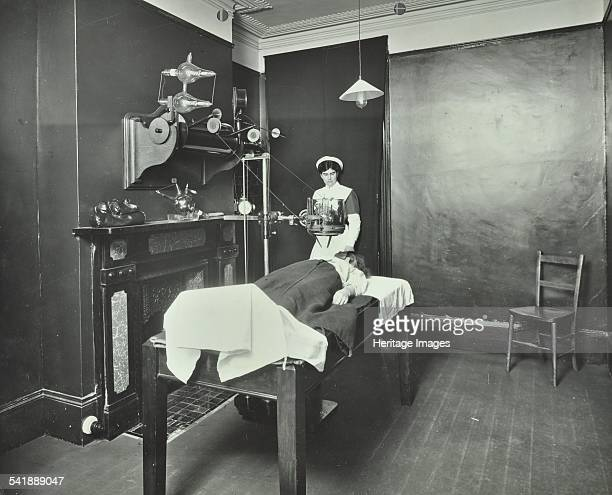 Xray room Fulham School treatment centre London 1914 With a patient being treated and a nurse standing by the window Artist unknown