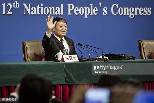 Xu Shaoshi chairman of the National Development and Reform Commission waves during a news conference on the sidelines of the fourth session of the...
