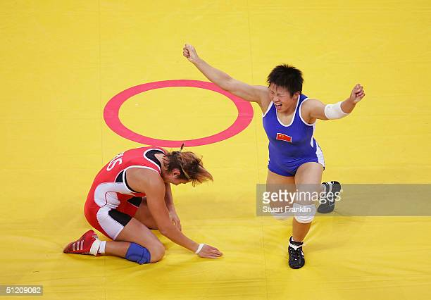 Xu Wang of China celebrates beating Gouzel Maniourova of Russia in the women's Freestyle wrestling 72 kg gold medal match on August 23, 2004 during...