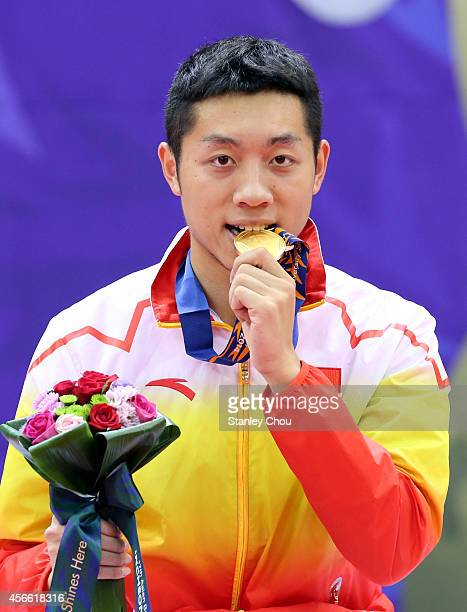 Xu Xin of China bites his Gold Medal during the victory ceremony after he defeated his compatriot Fan Zhendong during the Men's Singles Gold Medal...