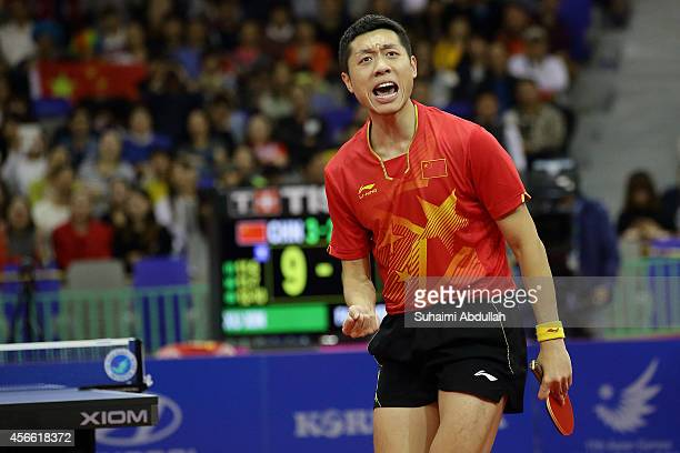 Xu Xin of China celebrates a winning point over Fan Zhengdong of China in the men's singles finals gold medal table tennis match on day fifteen of...