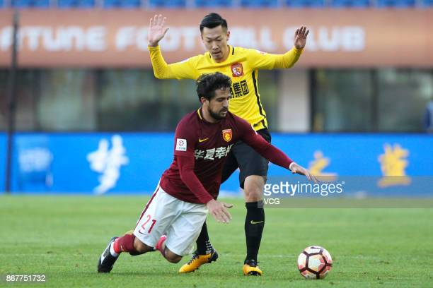 Xu Xin of Guangzhou Evergrande and Aloisio of Hebei China Fortune compete for the ball during the Chinese Super League match between Hebei China...