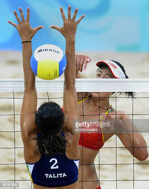 Xue Chen of China spikes the ball through the outstretched arms of Talita Antunes of Brazil in the bronze medal women's beach volleyball match at the...