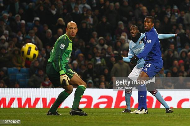 Ya Ya Toure of Manchester City scores his teams first goal past Tim Howard of Everton during the Barclays Premier League match between Manchester...