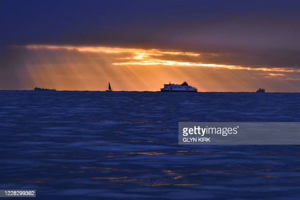 A yacht and a PO crosschannel ferry are seen in the Channel at sunrise off the southeast coast of England on September 1 2020