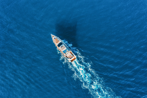 Yacht at the sea in Europe. Aerial view of luxury floating ship at sunset. Colorful landscape with boat in marina bay, blue sea. Top view from drone of yacht. Luxury cruise. Seascape with motorboat 911898354