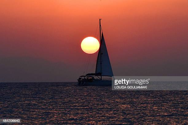 A yacht cruises as the sun rises off the Greek Aegean sland of Kos on August 16 2015 AFP PHOTO / LOUISA GOULIAMAKI